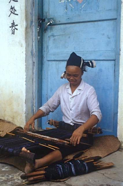 Matron weaving an ikat skirt on backstrap loom outside her front door, 1986